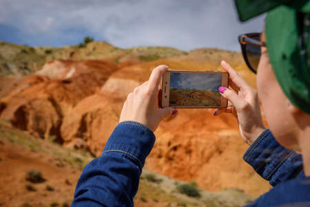Close-up of female tourist shoots amazing natural phenomenon on her smartphone. Martian landscapes in the Altai mountains. Travel to Russia. 版權商用圖片
