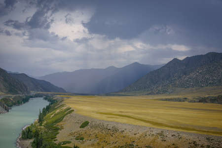 Majestic mountain landscape on a rainy summer or autumn day. Beautiful view of the bend of Katun river, plains and rocks. Torrents of rain, overcast sky. Natural backgrounds. 版權商用圖片 - 154877061