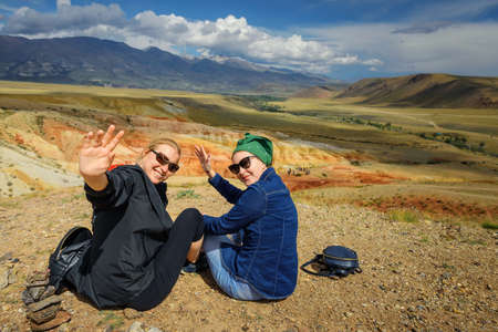 Two young women in sunglasses on hill waving arms and smiling. Female travelers are photographed against the beautiful mountains on sunny day. Active recreation and adventure.