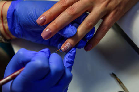 Covering the nails with gel polish, drawing picture on the nail plate. Manicurist in blue gloves apply varnish with a thin brush. Manicure in pastel colors.