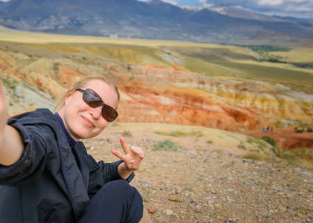 Female traveler takes a selfie sitting on hill on the background of Martian landscapes in Altai mountains. Young girl smiles the camera and shows hand gesture. Image for advertising with copy space.