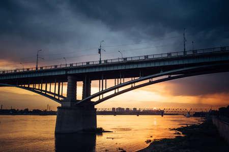 Urban evening landscape. Road bridge over the Ob river at sunset. Fantastic clouds in the dark sky.
