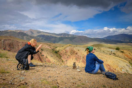Female tourist takes photos of her friend on smartphone at a beautiful vantage point. Two young women traveling in the mountains. Freedom, technology, adventure, discovery. 版權商用圖片