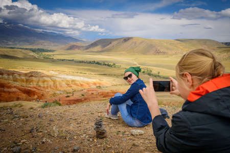 Female tourist takes photos of her girlfriend on smartphone at a beautiful vantage point, close up, selective focus. Traveling in the mountains. Freedom, technology, adventure, discovery. 版權商用圖片
