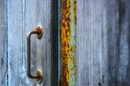 Fragment of an old wooden door with a rusty metal handle. Village gate, close-up. 版權商用圖片