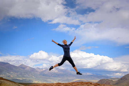 Young woman enjoying life and jumping against blue sky and mountains background. Happy female tourist jumps with hands up on top of rock on summer sunny day. Travel, freedom concept.