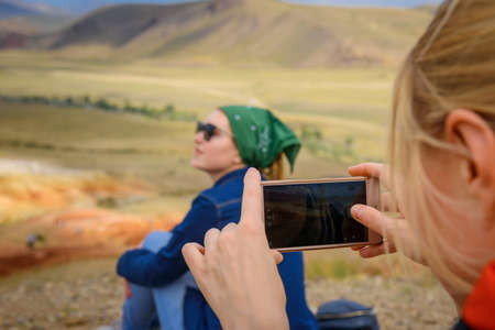 Female tourist takes photos of her girlfriend on smartphone at a beautiful vantage point, close up, selective focus. Traveling in the mountains. Freedom, technology, adventure, discovery. 版權商用圖片 - 154875654