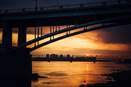Urban evening landscape. Road bridge over the Ob river at sunset. Fantastic clouds in the dark sky. 版權商用圖片 - 154876730