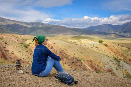 Young woman in jeans and sunglasses sitting against beautiful mountains and blue sky on sunny day. Freedom, tourism, adventure, discovery, travel available to ordinary people.