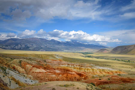Fantastic deserted mountain landscape on sunny day. Colorful rocks under blue sky with white clouds. Wild and lost corners of the planet, Martian landscape in the Altai.
