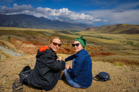 Two young girls in sunglasses sitting on hill look at camera and smile. Women travelers are photographed against the beautiful mountains on sunny day. Active recreation and adventure. 版權商用圖片
