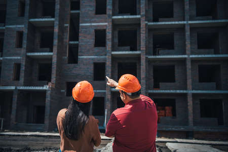 Rear view builders a man and a woman in orange helmets stand on the background of a brick apartment building under construction. Foremen monitor the progress of construction of the object. 版權商用圖片 - 154875072