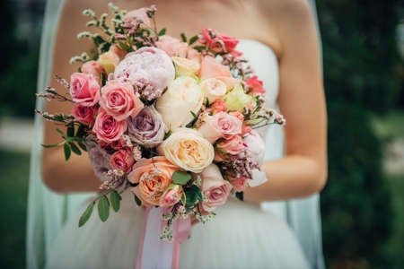Luxury wedding bouquet of fresh flowers in the hands of bride, close-up. Delicate roses in a beautiful bouquet, blurry background. 版權商用圖片 - 154875039