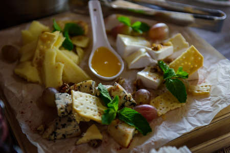 Cheese plate decorated with fresh mint leaves, close-up. Delicious appetizers of different types of cheese served with honey, cracker and grapes. Perfect accompaniment to wine.