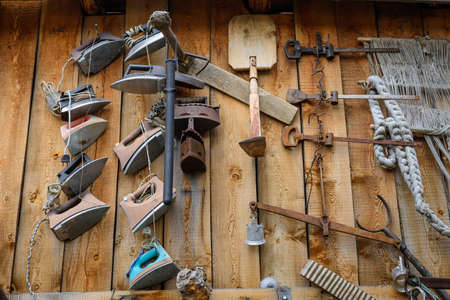 House-museum with old items from traditional rustic life. Vintage irons on the wooden wall, close up. Abstract retro image for the background.