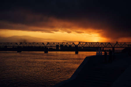 Urban evening landscape. Railway bridge over the river at sunset. Fantastic clouds in the dark sky.