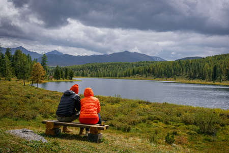 Couple in hooded jackets sitting on a bench, backs to the camera against the backdrop of beautiful lake in the mountains. Guy and girl resting, admiring the landscape. Travel, outdoor activities.