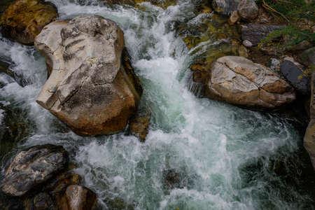 Rapid and powerful water flow between large rocks, close-up. Boulders in cold mountain river. Natural backgrounds. 版權商用圖片