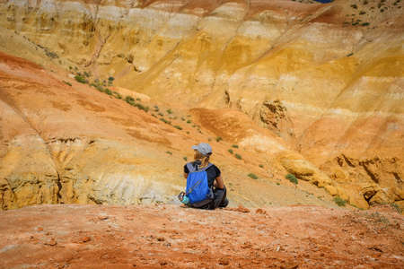 Young slender girl traveler on the background of fantastic Martian landscape in Altai mountains. Woman in cap with backpack sitting on hill admiring beautiful view. Freedom, travel to amazing places.