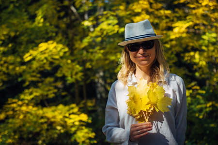 Beautiful elegant woman in white shirt and hat standing and smiling with bouquet of yellow leaves in autumn city park. Indian summer, golden autumn.