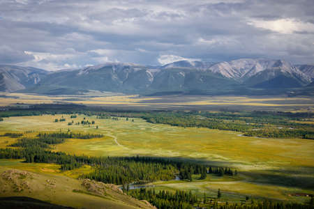 Picturesque green valley in sunlight against snowy mountain range under cloudy sky on summer or autumn day. Beautiful panorama of the Altai mountains, Siberia. 版權商用圖片