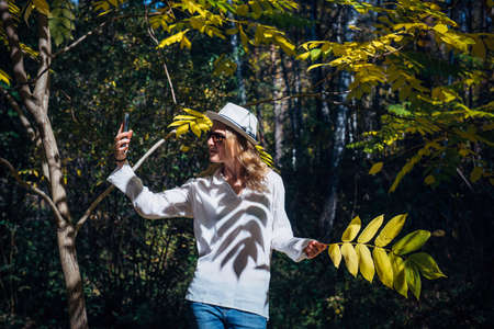Blonde in white shirt and hat takes a selfie on sunny autumn day. Young pretty woman walking in beautiful park among trees with yellow leaves.