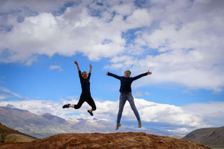 Two young happy girls jump raising hands up with spectacular view of mountains. Female travelers full of joy against the mountains and blue sky with white clouds. Lifestyle in motion concept.