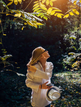 Cute blonde in white shirt with hat in her hand in the sunlight enjoying a walk in the park on beautiful autumn day. Young woman touches her hair and smiles. 版權商用圖片