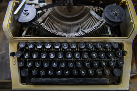 Black keyboard of a vintage typewriter with the Cyrillic alphabet. Close-up of rusty soviet typewriter with Russian letters.