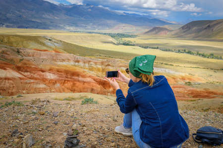 Female tourist takes pictures of amazing natural phenomenon on her smartphone. Colorful mountains in the Altai. Travel in Russia. Unknown planet.