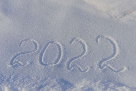 Coming 2022 year outlined on the snow winter background. Inscription 2022 on the snowdrift in sunlight. New Year's date design.