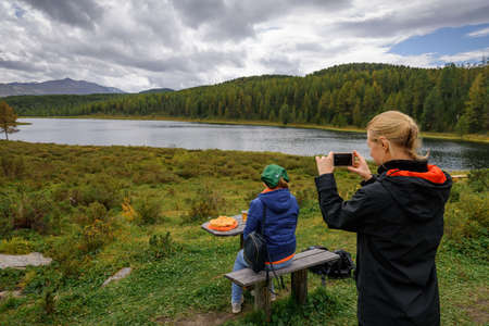 Young woman blogger takes a photo of her friend from behind against mountain lake. Tourist picnic on the background of beautiful mountains covered with coniferous forest.