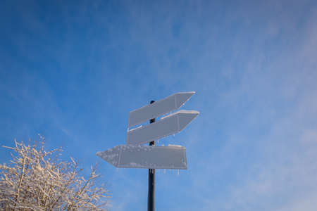 Blank signpost with three white arrows against beautiful blue sky in sunny frozen day. Blank track pointers or guide post on winter background with copy space. Icicles on signpost in sunlight.