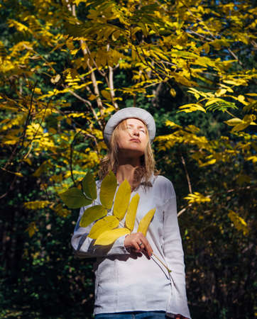 Blonde in white shirt and hat walks in beautiful park on sunny autumn day. Young pretty woman holds a branch with yellow leaves in her hand. Harmony with nature, the benefits of vitamin D.