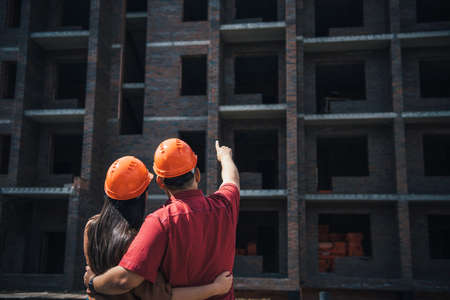 Back view a man and a woman in orange helmets stand with their arms around each other and look at a brick apartment building under construction. Investment in apartment, mortgage construction.
