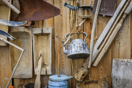 Set of various vintage items on wooden wall. Old dishes, metal kettle, household utensils. Traditional items of Slavic life. Abstract retro image for the background.