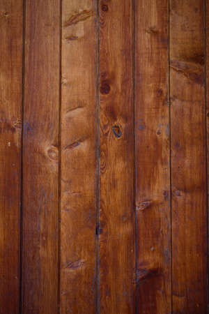 Old wooden background, close-up. Brown vertical boards. Facing the exterior walls of the house.