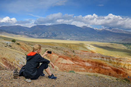 Young woman sitting on hill and taking photos on smartphone of a beautiful mountain landscape. Freedom, tourism, technology, adventure, discovery, travel for ordinary people. Image with copy space.