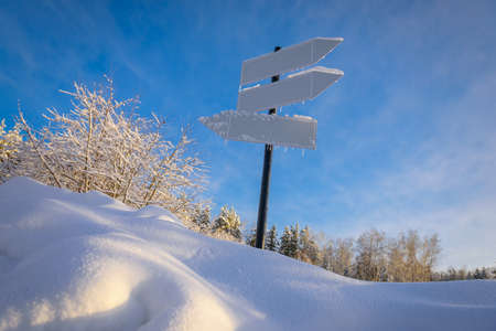 Blank signpost with three white arrows against beautiful blue sky in sunny frozen day. Blank track pointers or guide post on winter background with copy space. Icicles on signpost in sunlight. 免版税图像 - 157890171