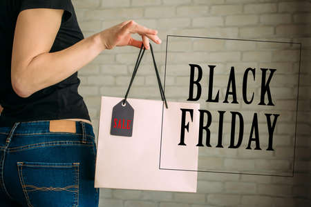 Woman holding a paper bag with tag black Friday. Back view of slender female butt in blue jeans. Concept of shopping, seasonal discounts. Advertising sign. 版權商用圖片