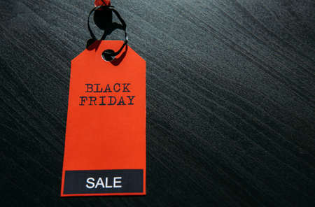 Red tag with inscription on dark wooden background in stylish design, close-up. Concept of black Friday. Final sale in America. Season of total discounts. Image for advertising with copy space.
