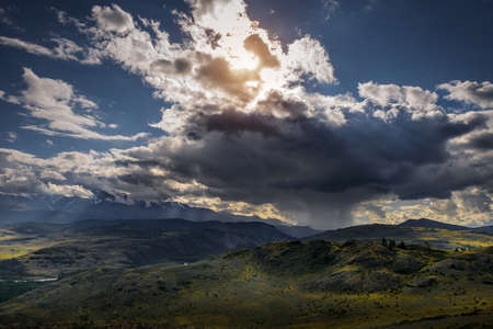 Majestic landscape. Rain clouds snowy peaks beautiful sky with sun rays. Storm sweeps over Kurai steppe in Altai mountains. Harsh climate of Siberia.