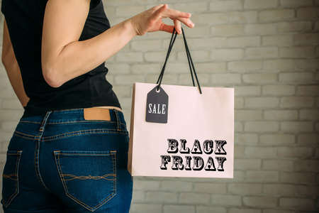 Cropped view sexy woman in denim holding paper bag with tag in her hand against a white brick wall in the mall. Copy space. Black Friday sale concept. 版權商用圖片
