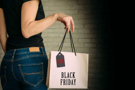 People, sale, black friday and consumerism concept. Close up of woman in jeans with paper shopping bag. Copy space. 版權商用圖片
