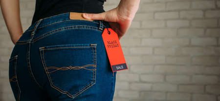 People, sale, consumerism concept. Close up cropped photo of sexual woman's buttocks wearing blue casual denim pants on gray brick background in the mall. Red tag black Friday on jeans.
