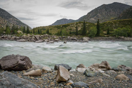 Rapid flow of water in mountain river on the background of rocks and overcast sky. Area for rafting, high level of difficulty. 版權商用圖片