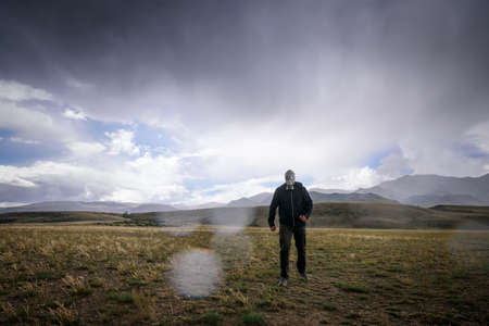 Strong man in black jacket and gas mask on the background of mountains, around the smoke, fog and radioactive fallout. Concept of environmental pollution, chemical disaster. Doomsday. 版權商用圖片