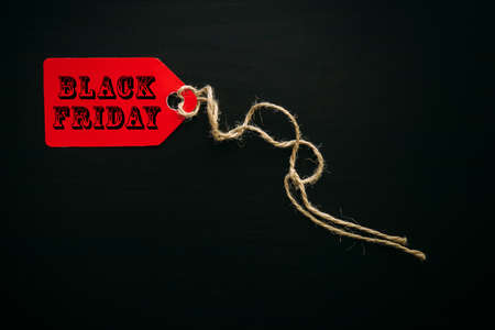 Black friday shopping sale concept. Text on red tag on black wooden background in sunlight. Copy space.