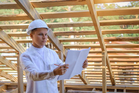 Foreman holding drawings, looking the project of wooden house, working on a construction site. Young attractive engineer in a white helmet checks the roof frame. Concept career architect. Copy space.