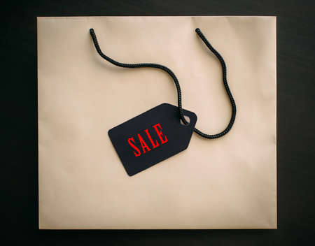 Paper bag with tag black friday isolated on black background, close up. Sales, shopping, consumerism concept. 版權商用圖片